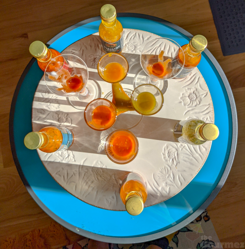 A circular display of African Dreams Hot Sauces in shot glasses with bottles.