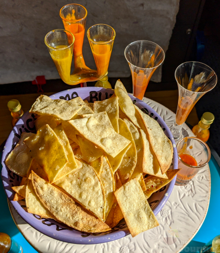A bowl of fresh tortilla chips surrounded by shot glasses